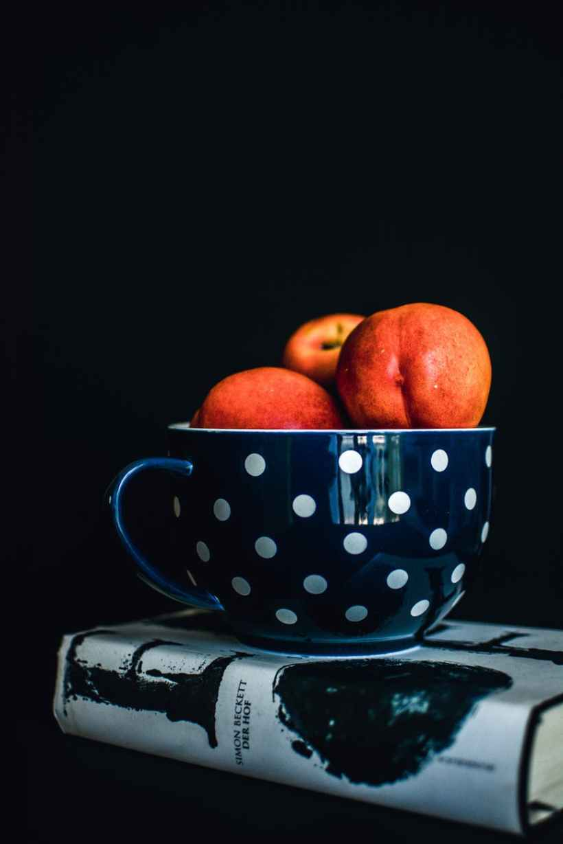three red apples on white and black polka dot mug